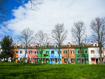 Colorful houses, leafless trees, green grass, Burano. Brightly multicolored painted houses with foreground of leafless trees and green lawn in a quiet area of stock photos