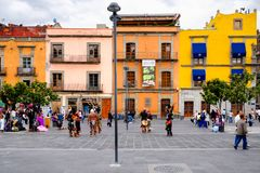 Colorful houses, people and street artists dressed as Aztecs in Mexico City. MEXICO CITY,MEXICO - JULY 12,2018 : Colorful houses, people and street artists royalty free stock photography