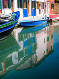 Colorful houses reflection on still water, Burano. Brightly colorful painted houses and floating boats with blue sky reflected on still water of a waterway in Royalty Free Stock Photos