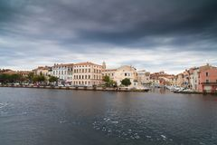 Canal in Venice and houses. Colorful houses standing on the banks of the canal in Venice. Black clouds. The rain is coming. Photo can become cover or background Royalty Free Stock Images