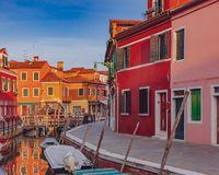 Colorful houses and streets by canal on the island of Burano, Venice, Italy, at sunset stock image