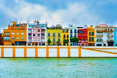 Colorful houses underneath a blue sky by the Guadalquivir river stock photo