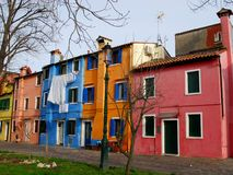 Colorful houses with white laundry in the island of Burano and the homonymous village of fishermen and embroideries in the municip Royalty Free Stock Images