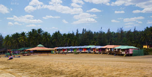 Colorful huts in Agonda beach with palm trees background in Goa, India Royalty Free Stock Image