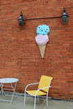 Colorful ice cream cone on brick wall with chairs and table. Colorful ice cream cone set on brick wall of building with table and chairs beneath, invites people Royalty Free Stock Images