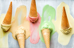 Colorful ice cream cones of different flavors. Melting scoops. Top view,  steel metal background. Stock Photos