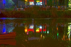 Colorful illuminated beer garden at night seen across a pond royalty free stock photos
