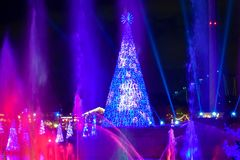 Colorful illuminated Christmas tree and waterjet on dark night background in International Drive area 1. Orlando, Florida. December 25, 2018. Colorful royalty free stock photos
