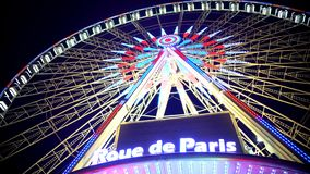 Colorful illuminated Rue de Paris observation wheel against night sky background. Stock footage stock photo