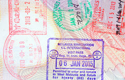 Colorful immigration arrival stamps on passport Royalty Free Stock Photos