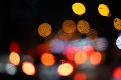 Colorful imperfect bokeh. Colorful red,blue,yellow,orange imperfect circle bokeh in rainy day on the road royalty free stock photography