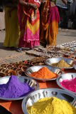 Colorful India. Colorful powders used for religious and cosmetic purposes shown in individual silver bowls, with women in traditional saris standing in the royalty free stock photos
