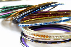 Colorful Indian Bangles. Many colors of bangles on top of a white shiny surface Royalty Free Stock Photography