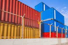 Colorful industrial cargo containers behind metal fence Royalty Free Stock Images