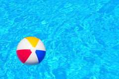 Colorful inflatable ball floating in swimming pool Royalty Free Stock Photos