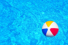 Colorful inflatable ball floating in swimming pool Stock Images