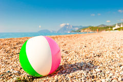 Colorful inflatable ball on a pebble beach Royalty Free Stock Photo
