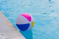 Colorful inflatable balloon on water surface. Ball in swimming pool royalty free stock photo