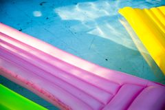 Colorful inflatable mattress in dirty swimming pool. Swimming pool with dirt and leaves on the bottom royalty free stock images