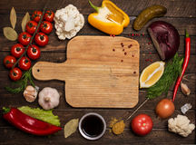 Colorful ingredients for cooking on rustic wooden table around e. Mpty cutting board with copy-space. Various vegetables and spices and empty old cutting board Stock Image