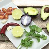 Avocado, onion, tomaten, chili, ingredients for guacomole royalty free stock photography