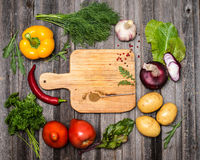 Colorful ingredients for vegetarian cooking on rustic weathered. Wooden table around empty cutting board with copyspace. Vegetables spices and herbs. Top view Royalty Free Stock Photos