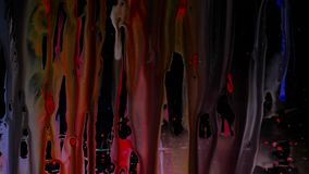 Colorful Ink droplets slide on glass. black background. stock footage