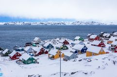 Colorful inuit houses among rocks and snow at the fjord in a sub Stock Photo