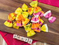 Colorful Italian butterfly pasta with the sign pasta on a wooden board Royalty Free Stock Photos