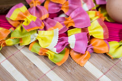 Colorful Italian butterfly pasta on a wooden board Royalty Free Stock Photos
