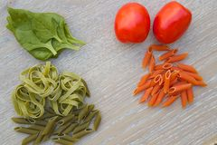 Colorful Italian raw pasta. Colorful Italian dried pasta and its compounds.Spinach and tomato pasta on the wooden surface Stock Photography