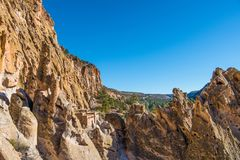 Colorful jagged rock formations, high cliffs, and ancient adobe ruins in Bandelier National Monument stock photography