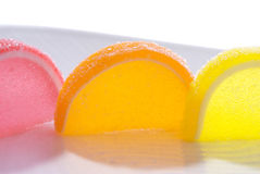 Colorful Jellied Fruit Candy Slices Macro. Pink, orange and yellow pastel slices of sugared jellied fruit candy slices standing on a white patterned plate Stock Photos