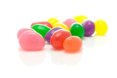 Colorful jelly bean sweets. Macro view of colorful group of jelly bean sweets receding into distance, isolated on white background Stock Photos