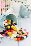 Colorful Jelly Beans. A blue tin bucket tipped over, spilling jelly beans onto a table. Shallow depth of field Royalty Free Stock Images