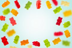Colorful jelly candy gummy bears falling over blue background stock photos