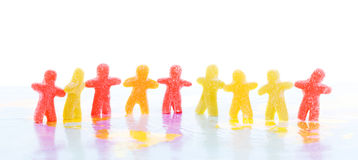 Colorful jelly people. Holding hands standing on a map Stock Image