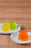 Colorful jelly on white plates over wooden background Stock Photography