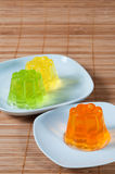 Colorful jelly on white plates over wooden background Stock Images
