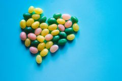 Colorful jellybeans candy in the shape of a heart on the blue background royalty free stock photo