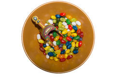 Colorful Jellybeans and Wooden Scoop in Bowl. Brown bowl with multi-colored jellybeans and colorful wooden scoop; isolated Stock Images