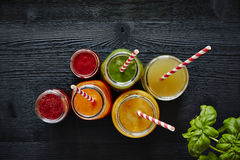 Colorful juice bar fresh organic healthy drinks. Red orange yellow and green variety of smoothies stock photography