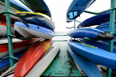 Colorful Kayaks and canoes in a Row stack Stock Photography