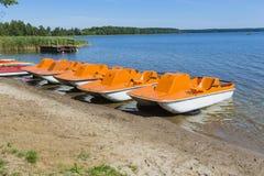 Colorful kayaks moored on lakeshore, Goldopiwo Lake, Mazury, Pol Stock Images