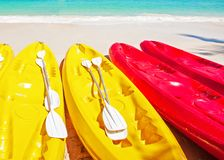 Colorful kayaks with paddles on a tropical beach in sunny summer, bright waves and turquoise seawater backgrounds. Vacations. Concept stock images