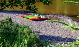 Colorful kayaks sitting on the shoreline by the lake Royalty Free Stock Image