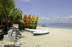 Colorful kayaks on tropical deserted white sandy beach at sunny day. Stock Image