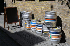 Colorful kegs of beer at the exit of a pub, on a brick wall Stock Photos