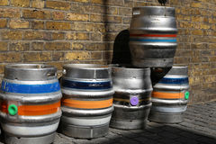 Colorful kegs of beer at the exit of a pub, on a brick wall Stock Photography