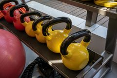 Colorful kettlebell lining on table or shelf in gym royalty free stock photos